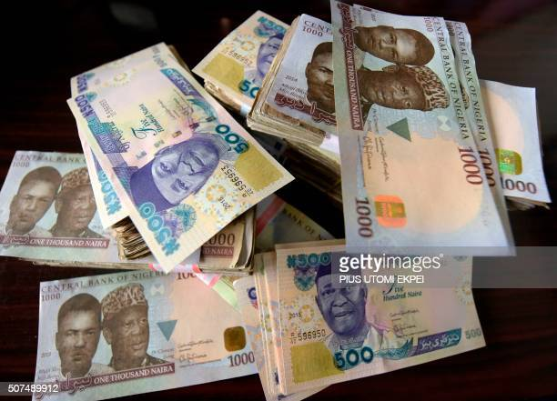 This picture taken on January 28 2016 in Lagos shows naira banknotes Nigeria's currency Nigeria's central bank governor Godwin Emefiele on January 26...