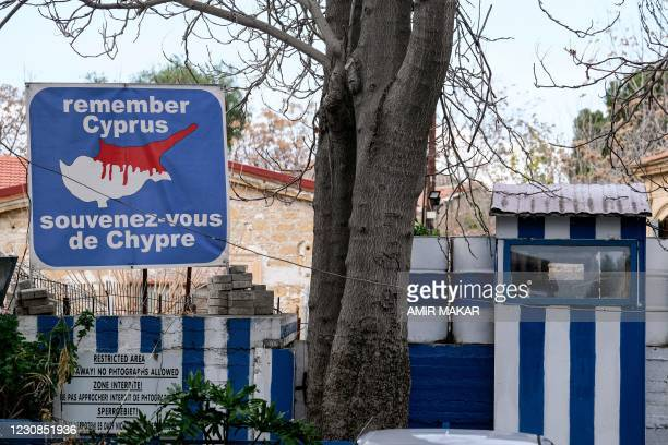 """This picture taken on January 28, 2021 shows a view of a sign reading in French and English """"remember Cyprus"""" and showing a map of the island of..."""