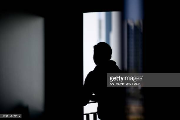 "This picture taken on January 29, 2021 shows a reflection of online entrepreneur ""Ian"", who is waiting to see how the Covid-19 coronavirus vaccine..."