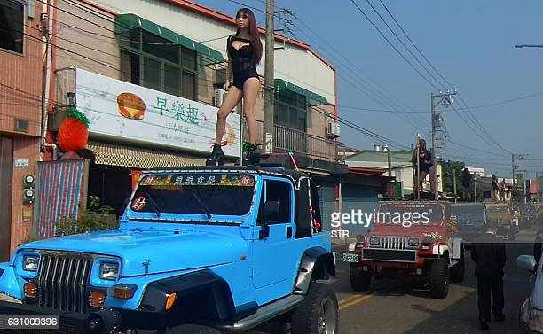 This picture taken on January 3 2017 shows pole dancers performing on top of jeeps during the funeral procession of former Chiayi City county council...