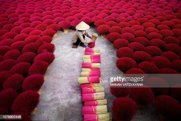 This picture taken on January 3, 2019 shows a Vietnamese woman collecting incense sticks in a courtyard in the village of Quang Phu Cau on the...