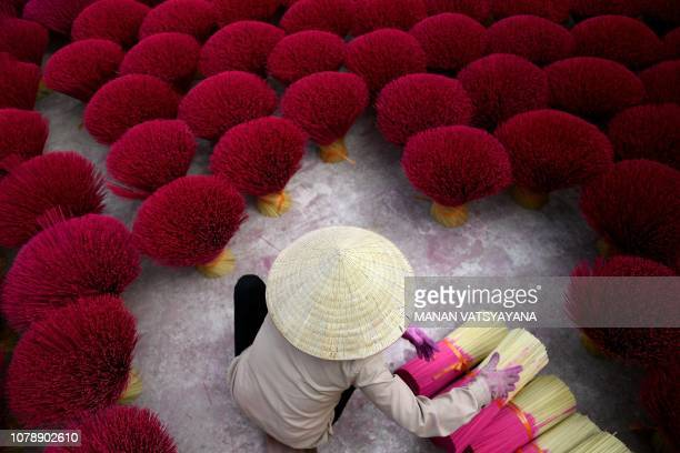 TOPSHOT This picture taken on January 3 2019 shows a Vietnamese woman collecting incense sticks in a courtyard in the village of Quang Phu Cau on the...