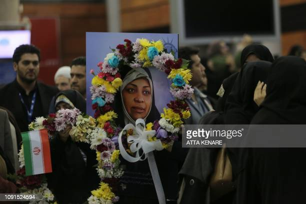 TOPSHOT This picture taken on January 30 2019 shows a painting of journalist Marzieh Hashemi as she arrives at Tehran Imam Khomeini International...
