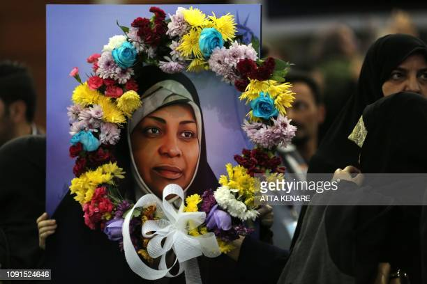 This picture taken on January 30 2019 shows a painting of journalist Marzieh Hashemi as she arrives at Tehran Imam Khomeini International Airport in...