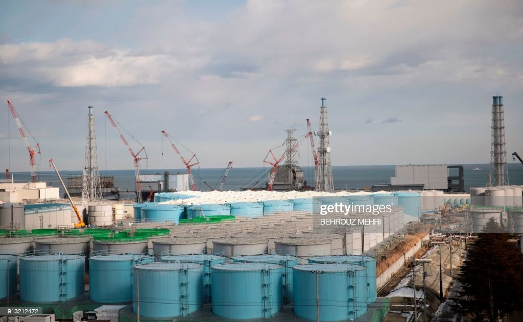 This picture taken on January 31, 2018 shows (from left) unit 1 to unit 4 reactor buildings and storage tanks for contaminated water at the Tokyo Electric Power Company (TEPCO) Fukushima Dai-ichi nuclear power plant in Okuma, Fukushima prefecture. The Fukushima nuclear power operator is hoping to use the 2020 Tokyo Olympics as a springboard to double the number of visitors to its Tsunami-ravaged plant, as it seeks to clean up the region's image. A massive undersea earthquake on March 11, 2011 sent a tsunami barrelling into Japan's northeast coast, leaving more than 18,000 people dead or missing and sparking the Fukushima crisis, the worst such accident since Chernobyl in 1986. PHOTO / Behrouz MEHRI / TO GO WITH AFP STORY 'JAPAN-NUCLEAR-FUKUSHIMA-DISASTER' BY