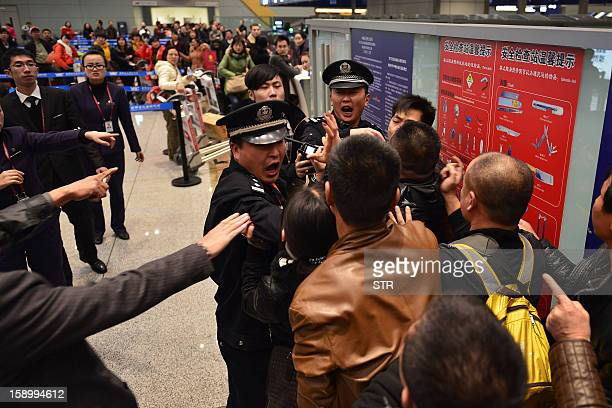 This picture taken on January 4 2013 shows stranded travellers arguing with police and airline personnel at Changshui International Airport in...