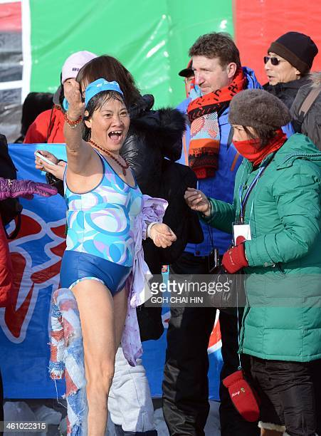 This picture taken on January 6 2014 shows a Chinese swimmer jubilating to her cheering fans after she won a race as she takes part in an ice...