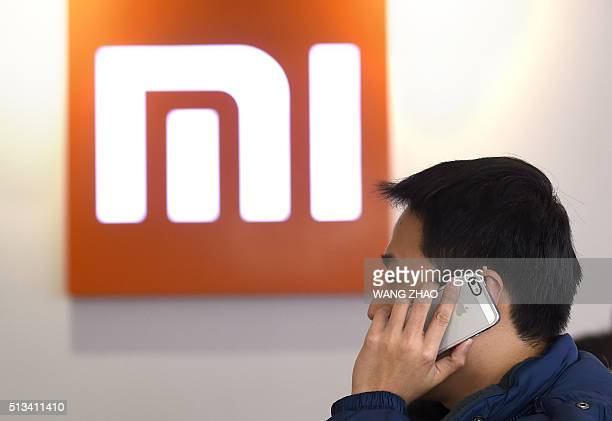 This picture taken on January 7, 2015 shows a man using his mobile phone at a Xiaomi shop in Beijing. AFP PHOTO / WANG ZHAO / AFP / WANG ZHAO