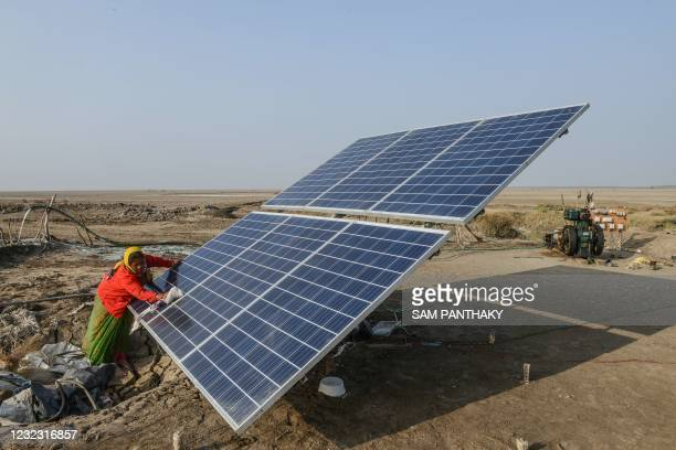 This picture taken on January 8, 2021 shows salt pan worker Sonalben cleaning a solar panel used in deriving saline water, in the Little Rann of...