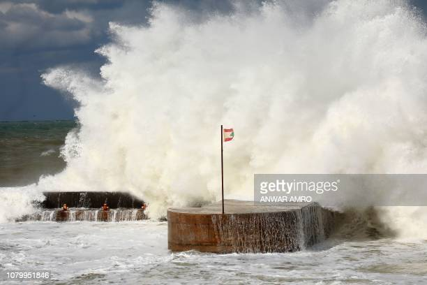 This picture taken on January 9 2019 shows a Lebanese flag flying on a dyke amidst crashing waves on the shote of the Lebanese capital Beirut's...