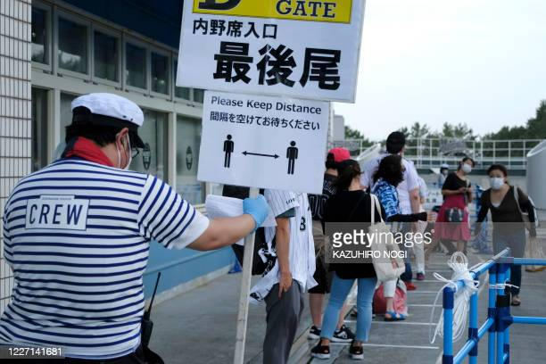 This picture taken on July 10, 2020 shows a worker holder a sign to maintain social distancing as baseball fans visit ZOZO Marine Stadium in Chiba...