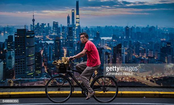 This picture taken on July 11 2016 shows a man cycling past a billboard showing an aerial view of Shanghai China's growth slipped to a new sevenyear...