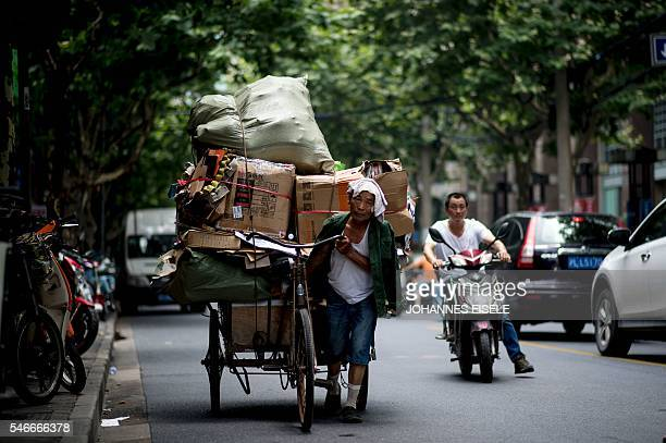 This picture taken on July 12 2016 shows a man pushing his loaded tricycle along the streets of Shanghai China's growth slipped to a new sevenyear...