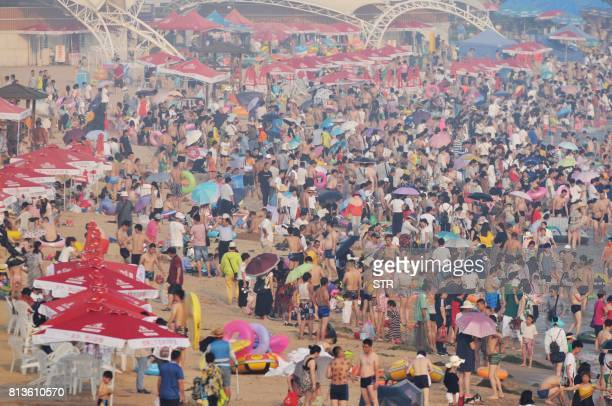 This picture taken on July 12 2017 shows beachgoers cooling themselves off amid high temperature on a beach in Qingdao east China's Shandong province...