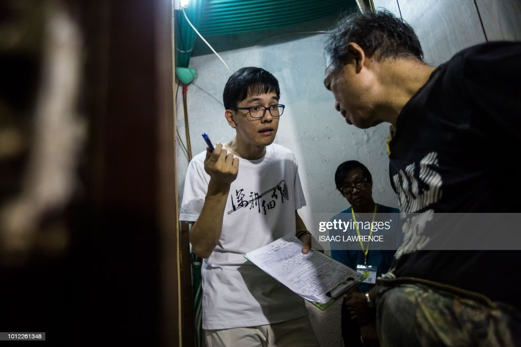 This picture taken on July 12, 2018 shows member Max Leung (L) speaking with a resident (R) of a subdivided flat who requested for his fridge to be repaired by Fixing Hong Kong, a pro-democracy community group, in the neighbourhood of To Kwa Wan in Hong Kong. - As attendance at Hong Kong's traditional protest rallies wanes, one pro-democracy group is trying to win hearts and minds in a more pragmatic way -- through plumbing, electrics and household repairs. Calling themselves Fixing Hong Kong, the group's volunteers mend broken appliances, furniture, pipes and wiring, hoping that forging community spirit will lead to greater political awareness. (Photo by Isaac LAWRENCE / AFP) / TO GO WITH Hong Kong-politics-lifestyle-social, FEATURE by Elaine YU