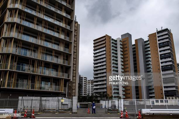 This picture taken on July 13, 2020 shows a security guard standing outside a section of the Olympic Athletes' Village in Tokyo. - Due to the...