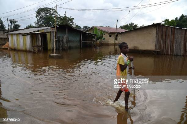 This picture taken on July 14 2018 shows a boy walking in a flooded area in Aboisso 120 kms from Abidjan after a heavy rainfall