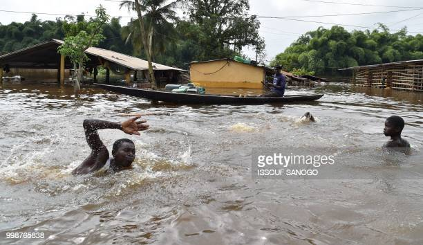 This picture taken on July 14 2018 shows a man swimming in a flooded area in Aboisso 120 kms from Abidjan after a heavy rainfall