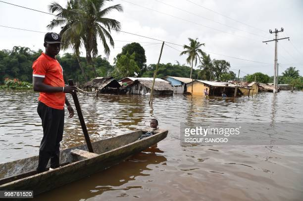This picture taken on July 14, 2018 shows a man walking in a flooded area in Aboisso, 120 kms from Abidjan after a heavy rainfall.