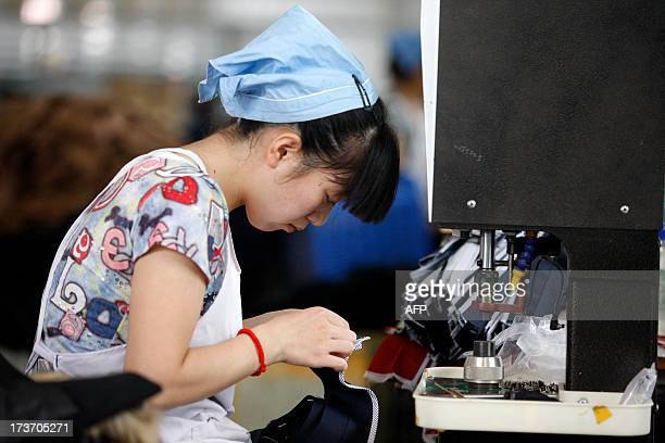 This picture taken on July 15, 2013 shows a laborer producing clothes waiting to be exported to EU in a factory in Huaibei, north China's Anhui...