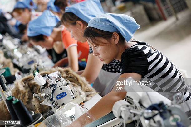 This picture taken on July 15, 2013 shows laborers producing clothes waiting to be exported to EU in a factory in Huaibei, north China's Anhui...