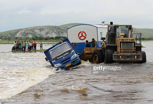 This picture taken on July 15 2013 shows vehicles trapped by floodwaters after heavy rain hit Hulunbuir north China's Inner Mongolia region At least...