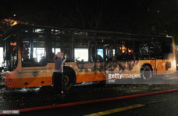 This picture taken on July 15 2014 shows investigators checking the debris of a bus which was allegedly set on fire by a man in Guangzhou in southern...