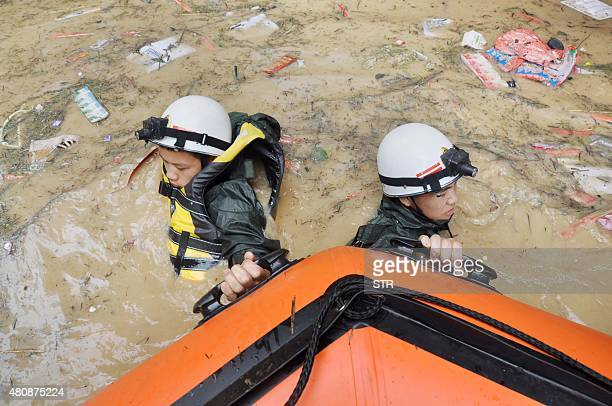 This picture taken on July 15 2015 shows rescuers pulling a boat through floodwaters after heavy rainfall hit the area in Songtao county in Tongren...