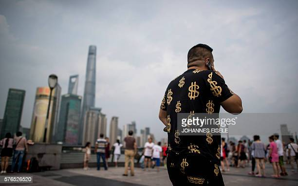 This picture taken on July 15 2016 shows a man wearing an outfit with golden dollar symbols as he walks down the Bund overlooking the financial...