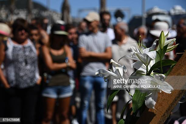 TOPSHOT This picture taken on July 15 2016 shows a white flower laid on the place where people gather to pay tribute to the victims the day after a...