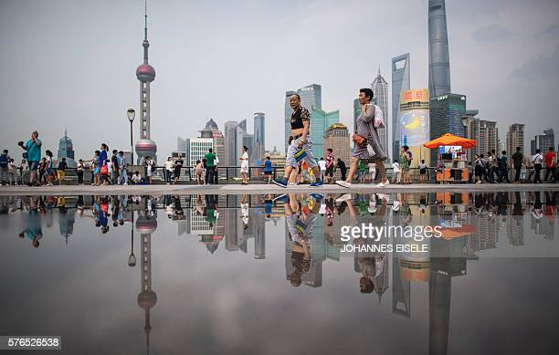 This picture taken on July 15 2016 shows people walking at the Bund overlooking the financial district of Pudong in Shanghai China's secondquarter...