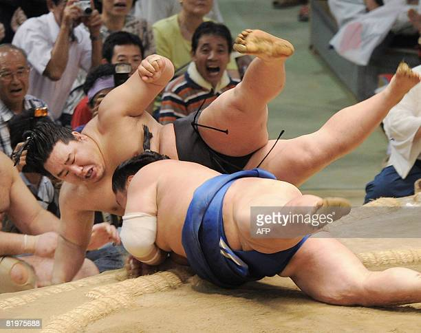 This picture taken on July 17 2008 shows Mongolian sumo grand champion Asashoryu being pushed out of the ring by Tochinonada during the fifth day...