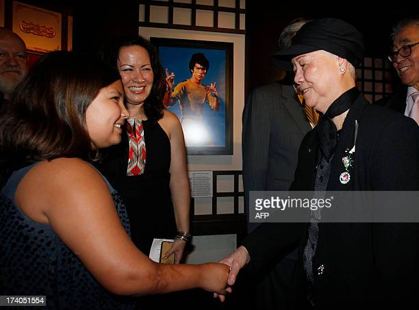 This picture taken on July 19 2013 shows Shannon Lee daughter of the late kung fu legend Bruce Lee looking on as her 10yearold daughter Wren shakes...