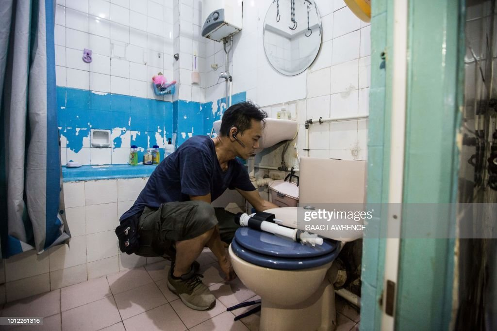 This picture taken on July 19, 2018 shows a volunteer plumber repairing a toilet for residents who have requested help from Fixing Hong Kong, a pro-democracy community group, in the neighbourhood of To Kwa Wan in Hong Kong. - As attendance at Hong Kong's traditional protest rallies wanes, one pro-democracy group is trying to win hearts and minds in a more pragmatic way -- through plumbing, electrics and household repairs. Calling themselves Fixing Hong Kong, the group's volunteers mend broken appliances, furniture, pipes and wiring, hoping that forging community spirit will lead to greater political awareness. (Photo by Isaac LAWRENCE / AFP) / TO GO WITH Hong Kong-politics-lifestyle-social, FEATURE by Elaine YU