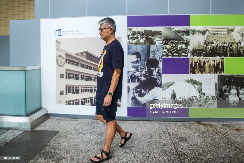 This picture taken on July 19, 2018 shows pro-democracy campaigner and political science assistant professor at Hong Kong Baptist University Benson Wong walking through the university grounds in Hong Kong, after receiving a letter in February from the university stating that his contract will not be renewed this year. - Pro-democracy Hong Kong academics say they have been sidelined from city universities for their political views as fears grow that education is increasingly under pressure from Beijing.