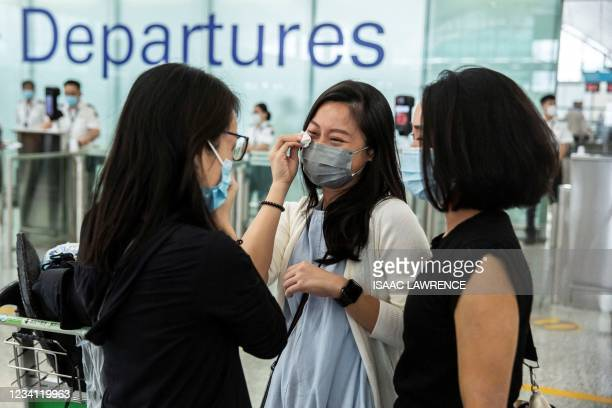 This picture taken on July 19 shows friends crying at the departure gates of Hong Kong's International Airport before one of them emigrates to...