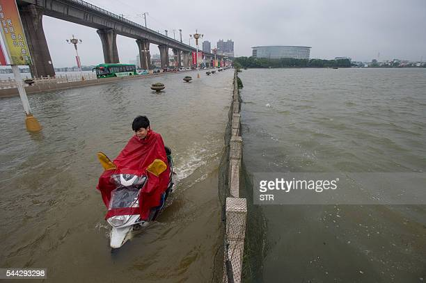 TOPSHOT This picture taken on July 2 2016 shows a man riding a scooter across a flooded bridge in Wuhan in China's central Hubei province Authorities...