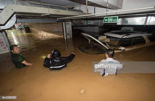 TOPSHOT This picture taken on July 2 2016 shows people trying to remove a car from a flooded parking garage in Wuhan in China's central Hubei...