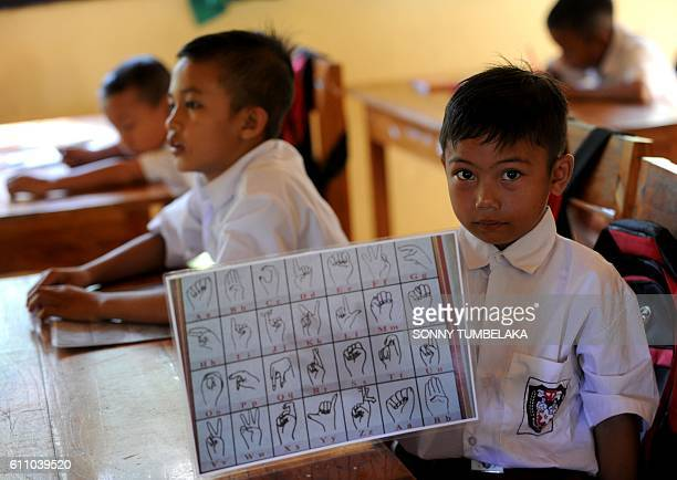 This picture taken on July 20 2016 shows a schoolboy holding a paper signs of alphabets for deaf during study in the class at an elementary school at...