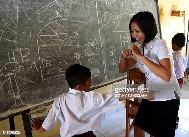 This picture taken on July 20 2016 shows a teacher speaking with sign language to a deaf school boy at an elementary school at Bengkala vilage in...