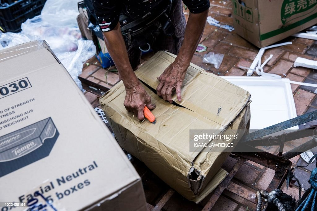 This picture taken on July 20, 2018 shows cardboard collector Au Fung-lan using a penknife to collapse cardboard boxes that she will sell to a recycling depot in the Kwai Fong district of Hong Kong. - Her fingers are bent from 20 years of collecting cardboard from Hong Kong's streets, but Au Fung-lan says she has no desire to give up the gruelling work. At 67-years-old she is one of around 2,900 collectors, mainly women over the age of 60, whose frail figures are a familiar sight, guiding trolleys loaded with cardboard through a city clogged with traffic and people. (Photo by Isaac LAWRENCE / AFP) / TO GO WITH HongKong-social-environment-elderly-cardboard-collector, FEATURE by Yan ZHAO
