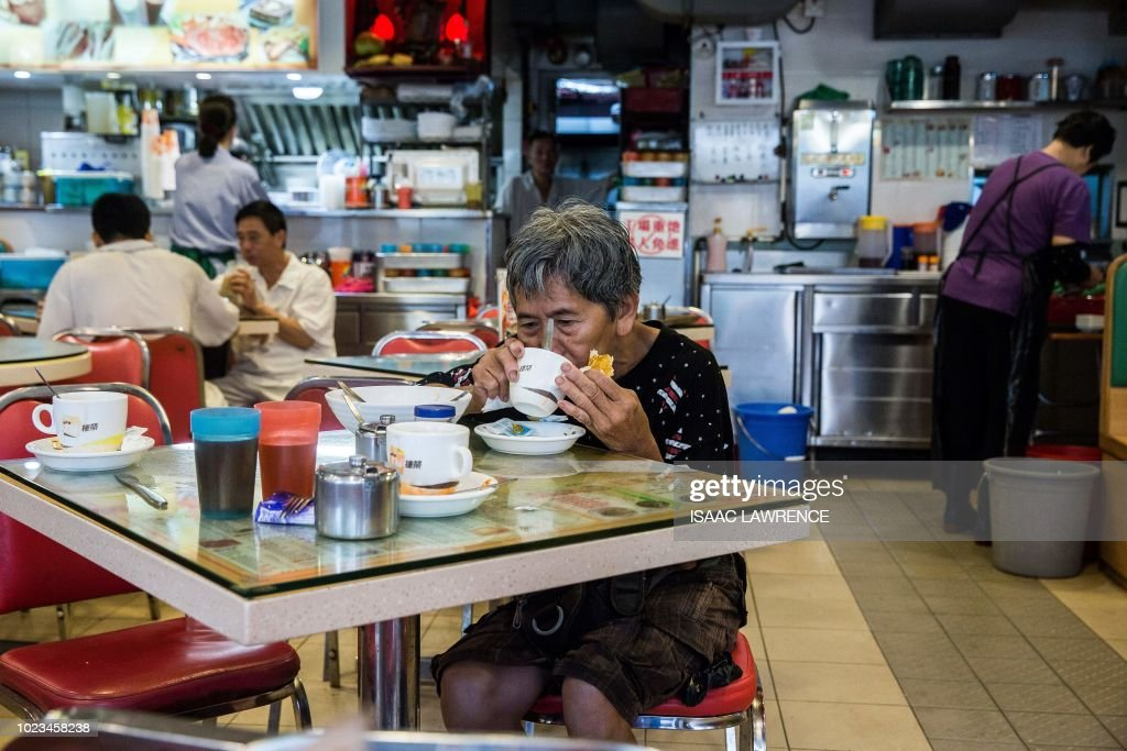 This picture taken on July 20, 2018 shows cardboard collector Au Fung-lan (C) taking a break from collecting cardboard to eat breakfast at a cafe in the Kwai Fong district of Hong Kong. - Her fingers are bent from 20 years of collecting cardboard from Hong Kong's streets, but Au Fung-lan says she has no desire to give up the gruelling work. At 67-years-old she is one of around 2,900 collectors, mainly women over the age of 60, whose frail figures are a familiar sight, guiding trolleys loaded with cardboard through a city clogged with traffic and people. (Photo by Isaac LAWRENCE / AFP) / TO GO WITH HongKong-social-environment-elderly-cardboard-collector, FEATURE by Yan ZHAO