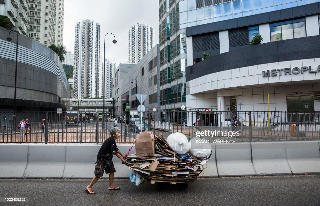 This picture taken on July 20, 2018 shows cardboard collector Au Fung-lan pushing her trolley full of cardboard along a road on her way to a recycling depot in the Kwai Fong district of Hong Kong. - Her fingers are bent from 20 years of collecting cardboard from Hong Kong's streets, but Au Fung-lan says she has no desire to give up the gruelling work. At 67-years-old she is one of around 2,900 collectors, mainly women over the age of 60, whose frail figures are a familiar sight, guiding trolleys loaded with cardboard through a city clogged with traffic and people. (Photo by Isaac LAWRENCE / AFP) / TO GO WITH HongKong-social-environment-elderly-cardboard-collector, FEATURE by Yan ZHAO