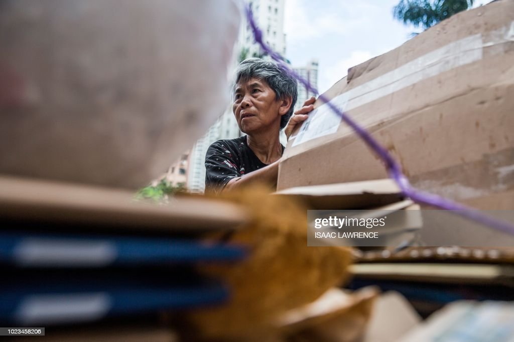This picture taken on July 20, 2018 shows cardboard collector Au Fung-lan sorting through rubbish in order to collect cardboard to sell to a recycling depot in the kwai Fong district of Hong Kong. - Her fingers are bent from 20 years of collecting cardboard from Hong Kong's streets, but Au Fung-lan says she has no desire to give up the gruelling work. At 67-years-old she is one of around 2,900 collectors, mainly women over the age of 60, whose frail figures are a familiar sight, guiding trolleys loaded with cardboard through a city clogged with traffic and people. (Photo by Isaac LAWRENCE / AFP) / TO GO WITH HongKong-social-environment-elderly-cardboard-collector, FEATURE by Yan ZHAO