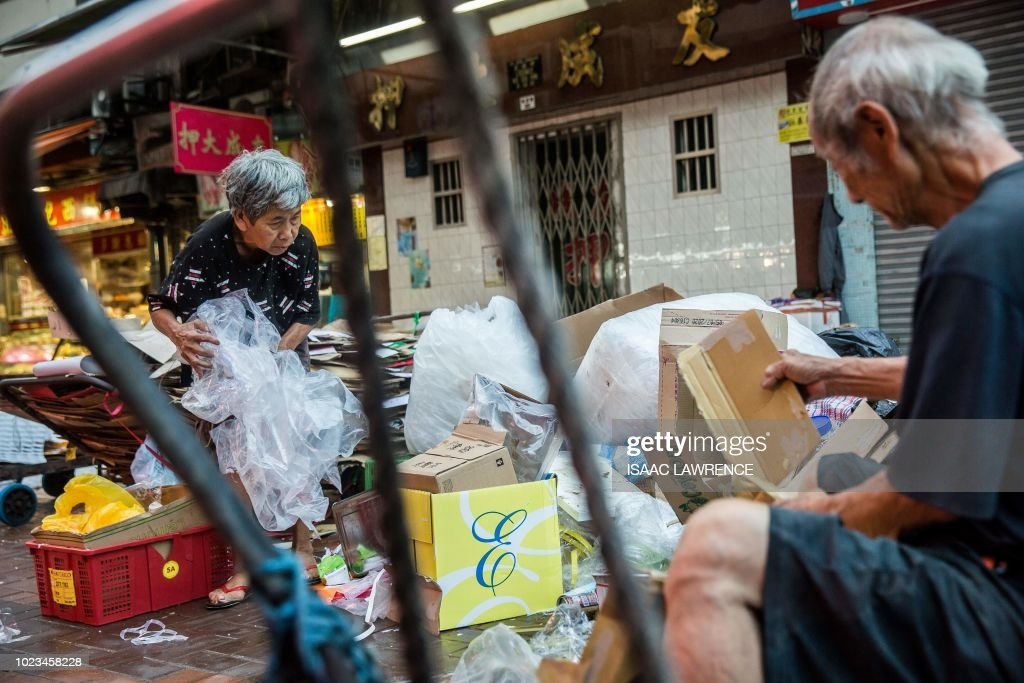 This picture taken on July 20, 2018 shows cardboard collector Au Fung-lan (L) sorting through rubbish in order to collect cardboard to sell to a recycling depot in the Kwai Fong district of Hong Kong. - Her fingers are bent from 20 years of collecting cardboard from Hong Kong's streets, but Au Fung-lan says she has no desire to give up the gruelling work. At 67-years-old she is one of around 2,900 collectors, mainly women over the age of 60, whose frail figures are a familiar sight, guiding trolleys loaded with cardboard through a city clogged with traffic and people. (Photo by Isaac LAWRENCE / AFP) / TO GO WITH HongKong-social-environment-elderly-cardboard-collector, FEATURE by Yan ZHAO