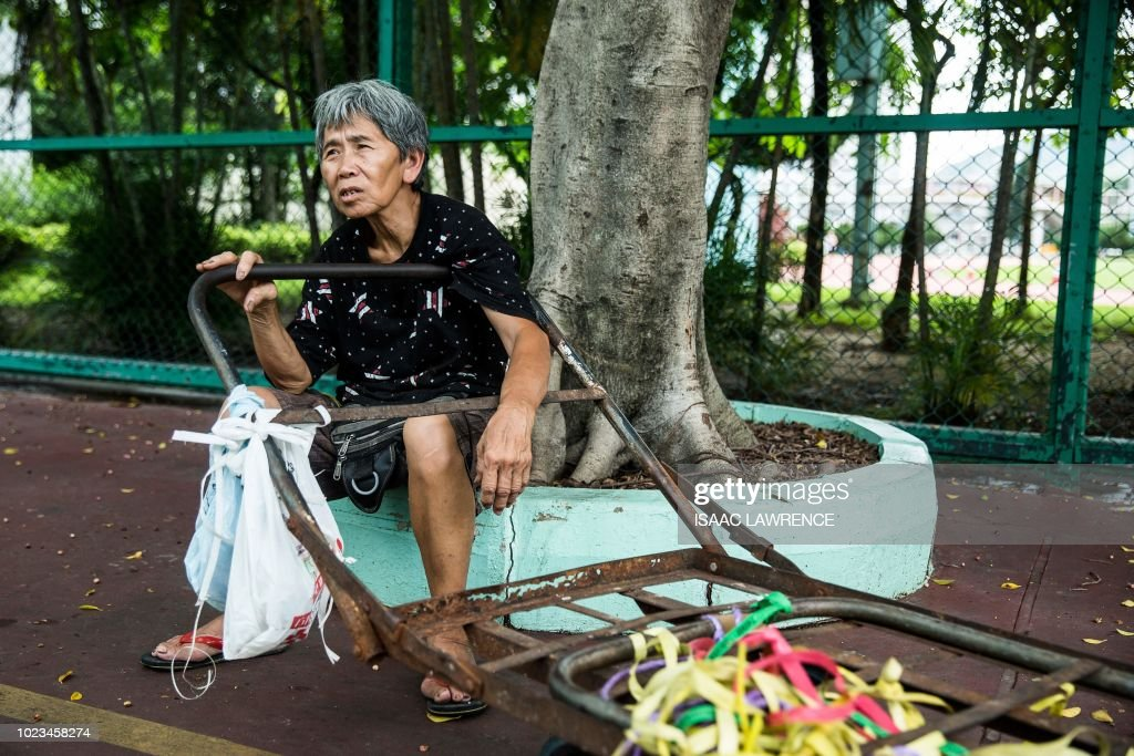 This picture taken on July 20, 2018 shows cardboard collector Au Fung-lan resting after dropping off a load of cardboard at a recycling depot in the Kwai Fong district of Hong Kong. - Her fingers are bent from 20 years of collecting cardboard from Hong Kong's streets, but Au Fung-lan says she has no desire to give up the gruelling work. At 67-years-old she is one of around 2,900 collectors, mainly women over the age of 60, whose frail figures are a familiar sight, guiding trolleys loaded with cardboard through a city clogged with traffic and people. (Photo by Isaac LAWRENCE / AFP) / TO GO WITH HongKong-social-environment-elderly-cardboard-collector, FEATURE by Yan ZHAO