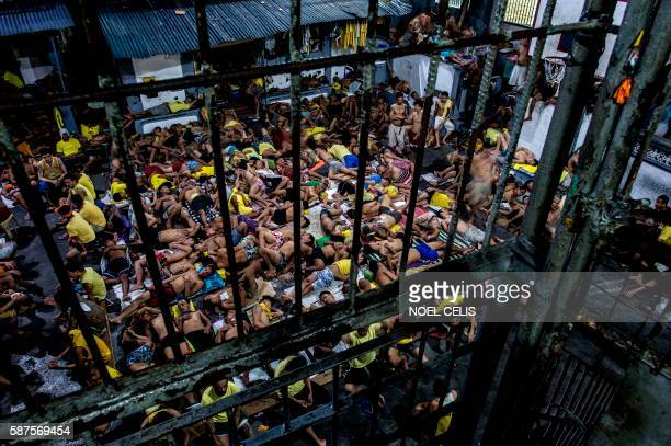 TOPSHOT This picture taken on July 21 2016 shows inmates sleeping at the open basketball court inside the Quezon City jail in Manila Philippine...