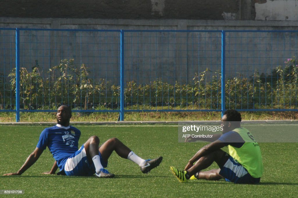 This picture taken on July 21, 2017 shows Persib football players Carlton Cole (L) and Michael Essien resting during a training session in Bandung. Former West Ham and Chelsea striker Carlton Cole is to be sacked by Indonesia's Persib after failing to find the net since his arrival in March, the team's manager said on August 1. /