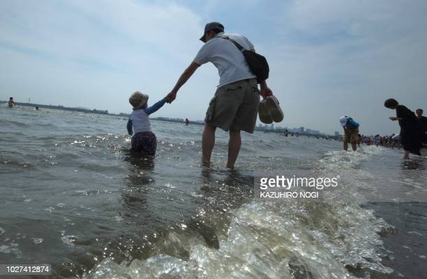 This picture taken on July 22 2018 shows a father and his son walking along the surf at the Kasai seaside park in Tokyo Bay On a blazing hot Tokyo...
