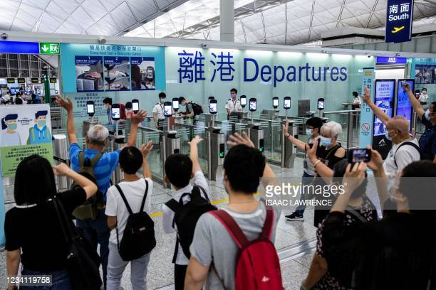 This picture taken on July 22 shows people waving goodbye as passengers make their way through the departure gates of Hong Kong's International...